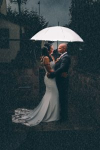 Bride and Groom sheltering from the rain